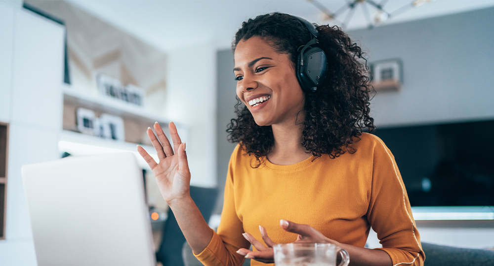Woman with headphones on smiling and waving at someone on the computer in a teleconference.